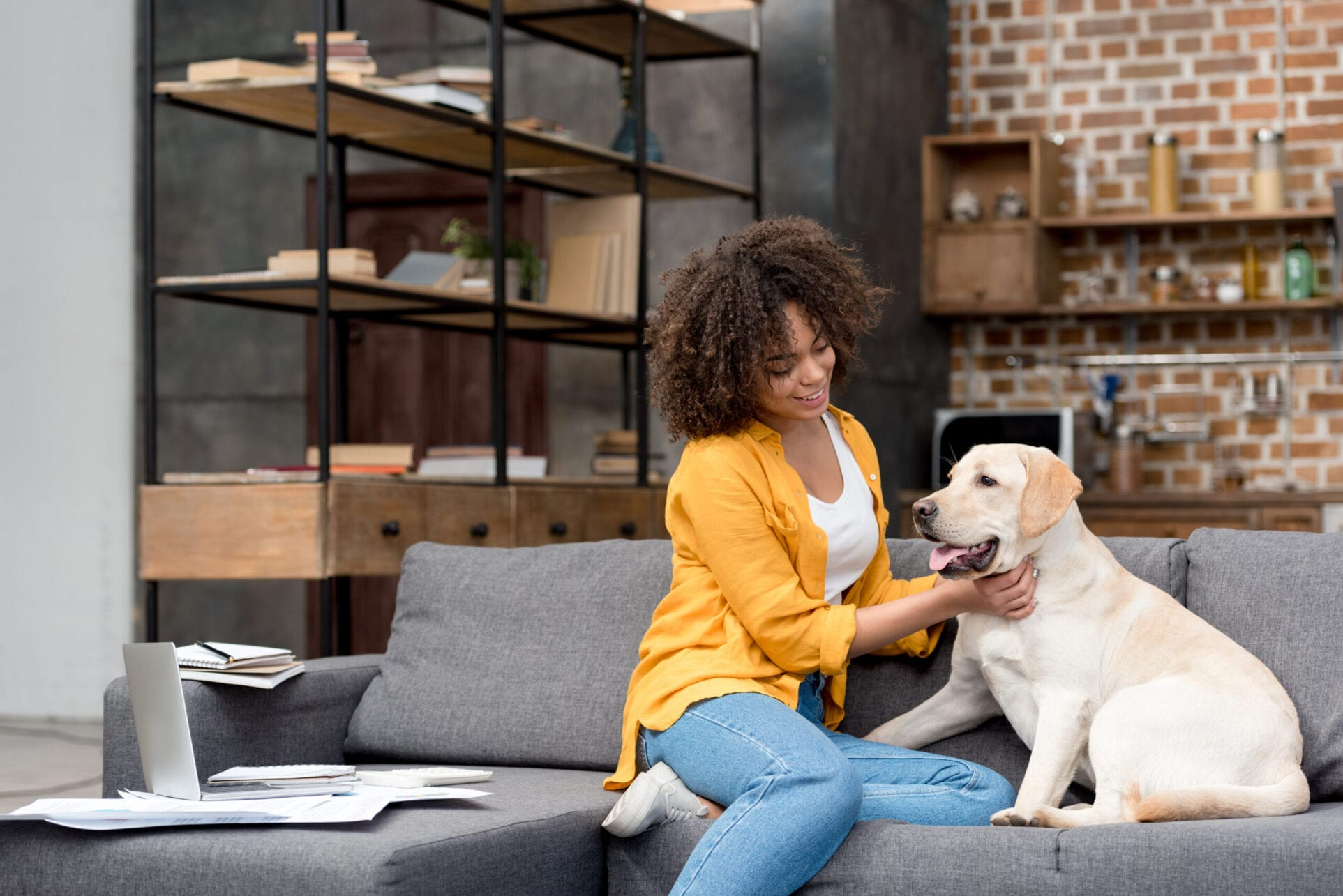 beautiful young woman working at home and petting her dog